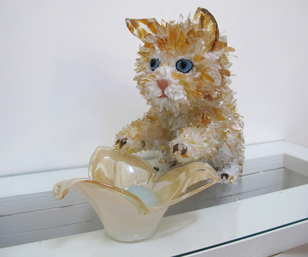 Kat Orange Tabby leaning on a bowl glass sculpture